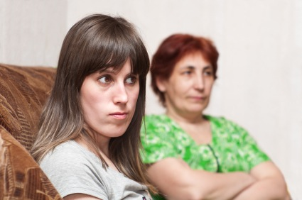 Mature woman a mother and young girl a daughter together on sofa